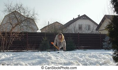 Woman cleans yard from snow with shovel