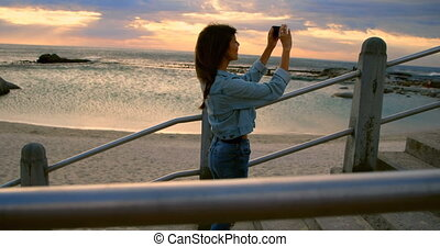 Woman clicking photos with mobile phone at beach 4k - Young...