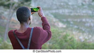 Woman clicking photos with mobile phone at countryside 4k -...
