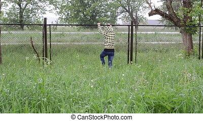woman climb fence rain