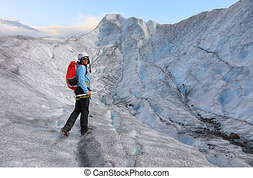 Woman climber standing in the cleft of the glacier