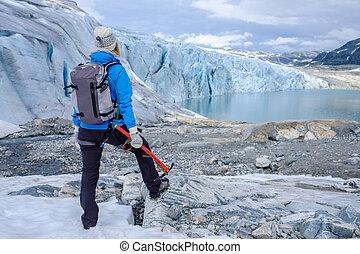 Woman climber standing near Jostedalsbreen glacier. Norway.