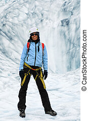 Woman climber stands in the cleft of the glacier