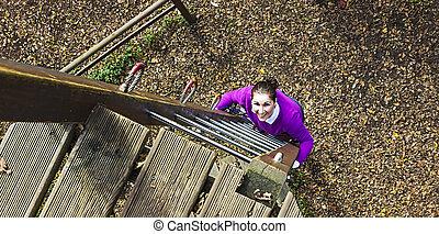 Woman climbing in adventure park