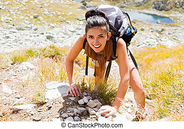 Woman Climbing Mountain - Woman enjoying climbing up a rocky...