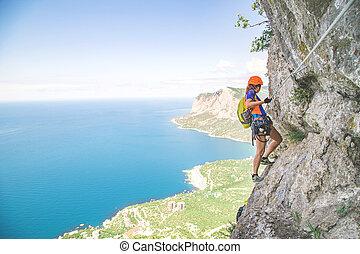 Woman climbing mountain.