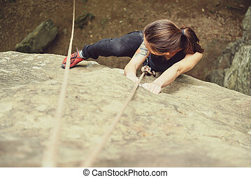 Woman climbing on rock mountain