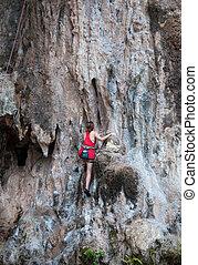 Woman climbing on the rock route summe (Railay Beach, Krabi province Thailand.