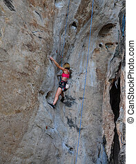 woman climbing on the rock route summer