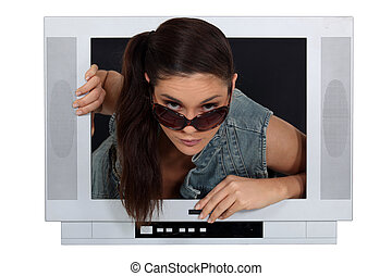 Woman climbing out of a TV set