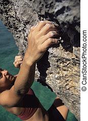 Woman climbing rocks in swimwear by ocean (selective focus)
