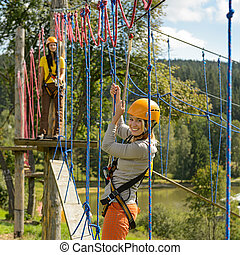 Woman climbing rope ladder in adventure park - Smiling woman...