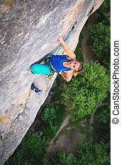 Woman climbs rock.
