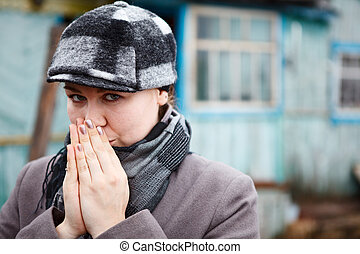 Woman close up portrait in cap and scarf with clasped hands. Copy space