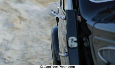Woman closes the door of a black retro car. Retro style video