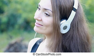 Woman closeup in headphones smiling and listening music