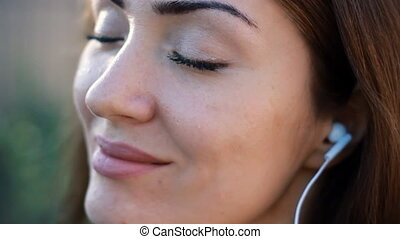 Woman closeup in headphones smiling and listening music with...