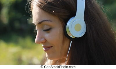 Woman closeup in headphones smiling and listening music. -...