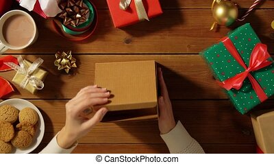woman closing empty christmas gift on wooden table - ...