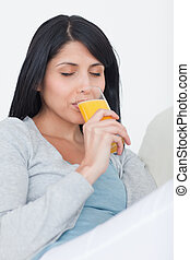 Woman closing her eyes while drinking from a glass of orange juice in a living room