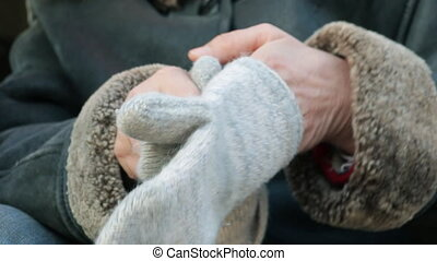 Woman clothes for hand knitted mittens - A woman in a warm...