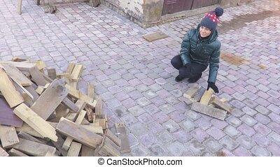 Woman collect firewood in yard