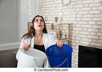 Woman Collecting Leaking Water In Bucket - Worried Woman ...