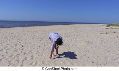 Woman collecting pebbles on sandy beach