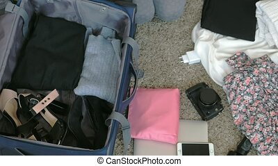 woman collects a suitcase in a home room.