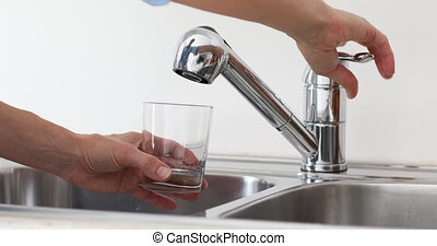 Woman collects water from the tap. - Woman collects pure...