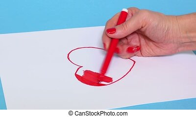 Woman coloring red heart shape on white paper