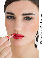 Woman colouring her lips