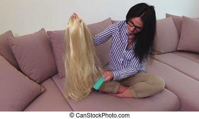 Woman combing blonde hair wig