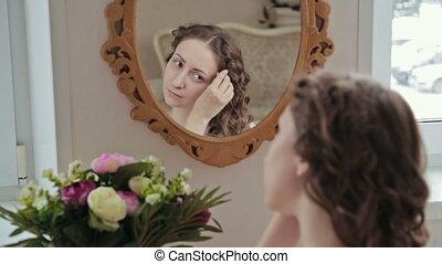 Woman combing hair near mirror