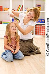 Woman combing little girls hair