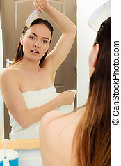 Woman combing wet hair after taking shower.