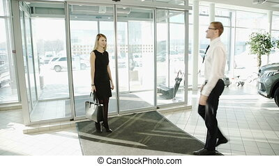 Woman come to showroom where it is at the door welcome at the dealer.