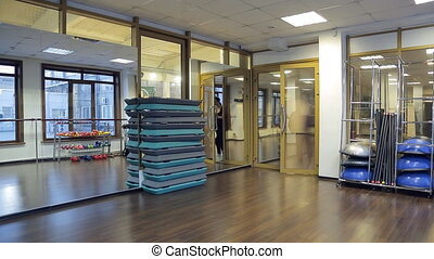 woman comes into fitness studio, gym mat spreads before...