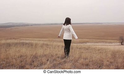 woman comes to the ravine her arms in nature open plain...