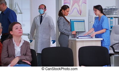 Woman coming at dental office asking for appointment sitting on chair in waiting room writing on registration document in stomatomoly clinic. Patients stitting in crowded orthodontist reception office