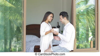 Woman Coming To Man Sitting On Window Sill, Couple Drinking Coffee Enjoy View From Bedroom In Morning