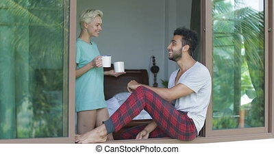 Woman Coming To Man Sitting On Window Sill, Couple Drinking Coffee Talk Enjoy View From Bedroom In Morning
