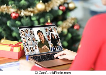 Woman communicating with group of business people by video link at home near Christmas tree close-up