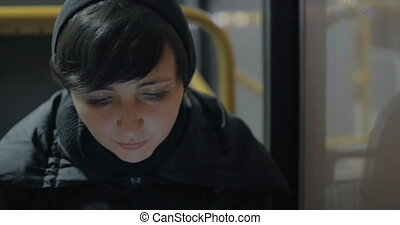 Woman commuter with mobile in the bus
