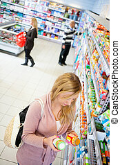 High angle view of a woman comparing products in a grocery store