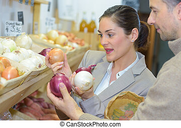 Woman comparing varieties of onions