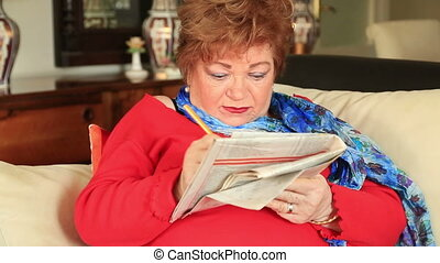 Woman completing crossword puzzle