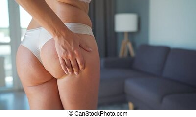 Woman compressing skin of the buttocks and checks for ...