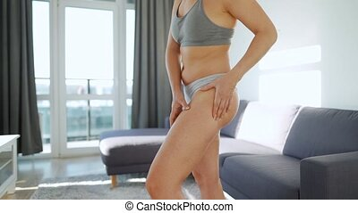 Woman squeezes the skin of the buttocks and legs checking for cellulite and excess subcutaneous fat. Concept of striving to meet generally accepted beauty standards