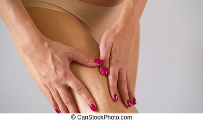 Woman compresses thigh skin and checks for stretch marks and cellulite
